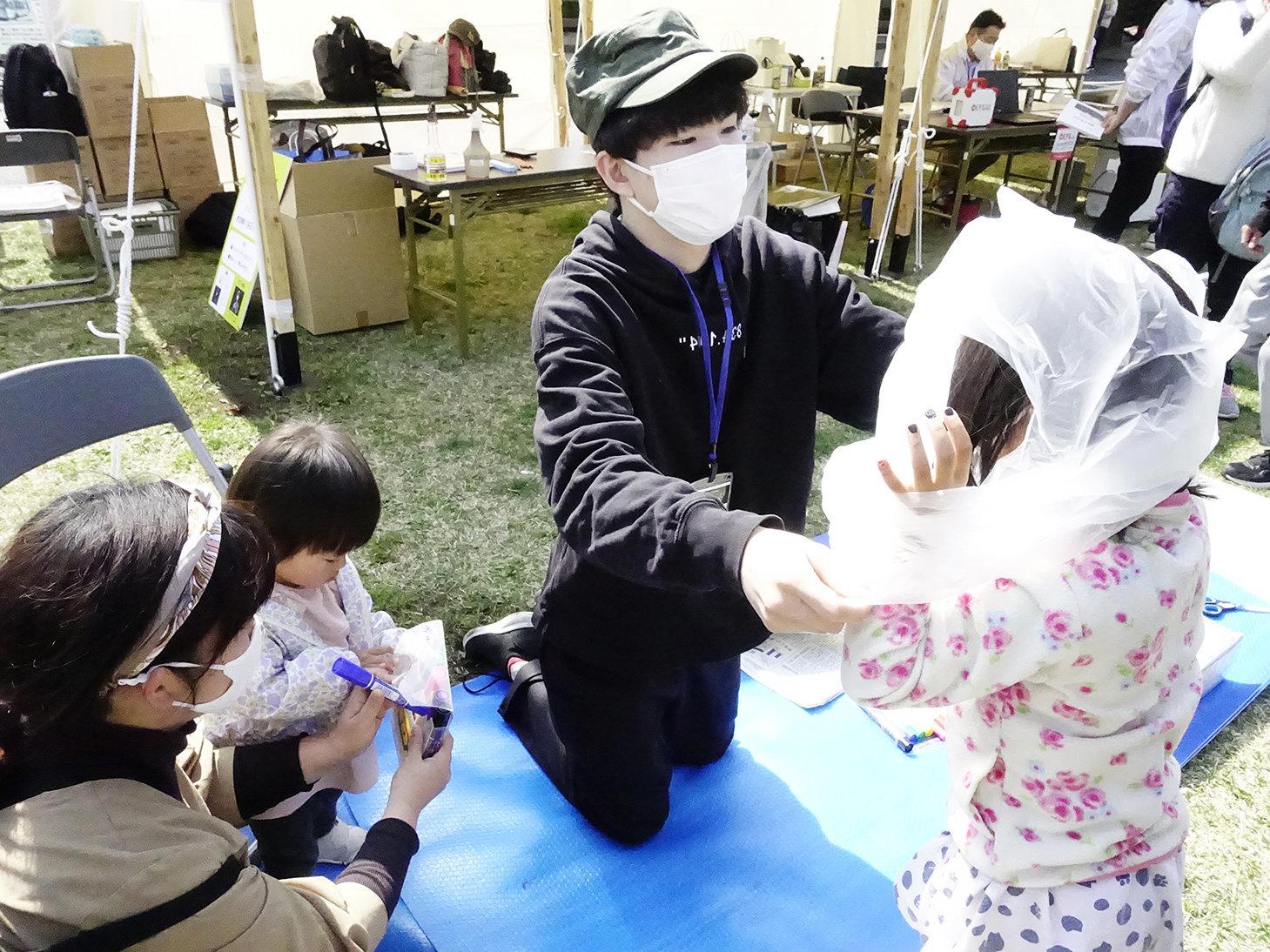 ゴミ袋を活用した防寒具の作り方を紹介する静岡大学学生防災ネットワークのメンバー(右から2人目)