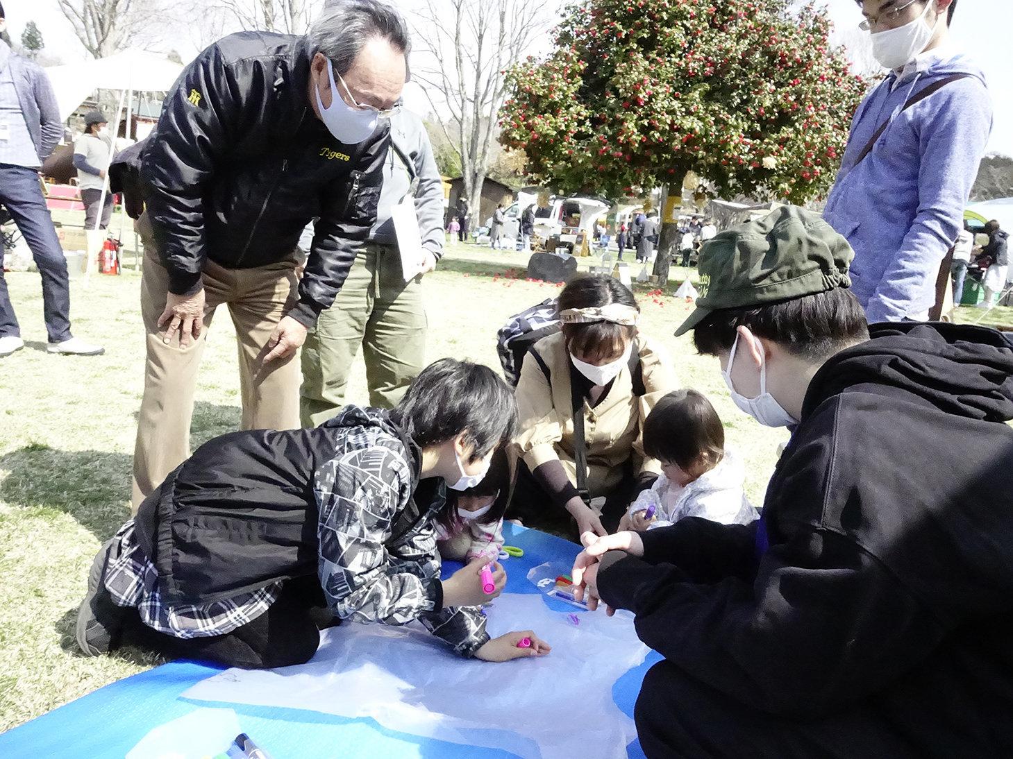静岡大学学生防災ネットワークのメンバー(手前右)に教わりながら防寒具作りに挑戦する来場者